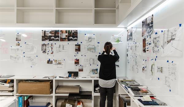a woman pins up architectural and interior desing sketches and technical details onto a whiteboard