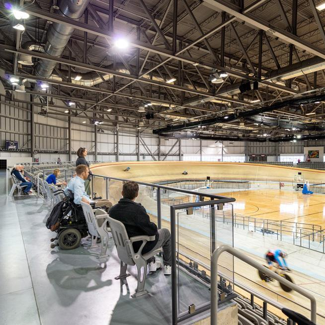 people with varying mobility needs watch from accessible viewing stands as cyclists ride a wooden track