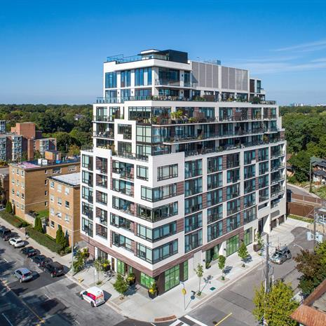 photo of the High Park condo, a white mid-rise building with inset balconies that tapers towards the top floor