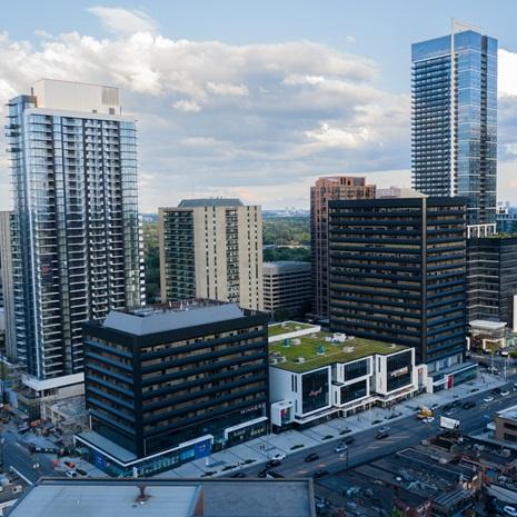 aerial photo of the Yonge Sheppard Centre after refurbishments showing black clad office buildings, modern white framed retail at grade, and a black and white high rise residential tower