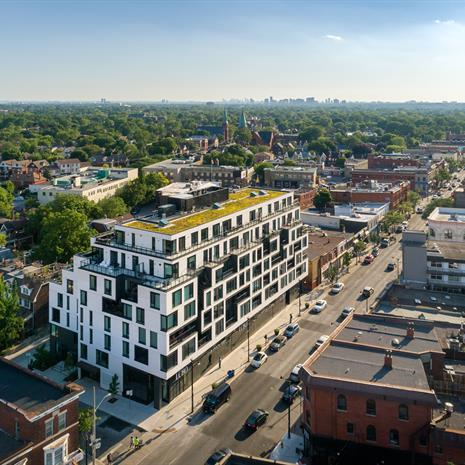 aerial photo of a white midrise condo with a green roof, surrounded by an urban streetscape