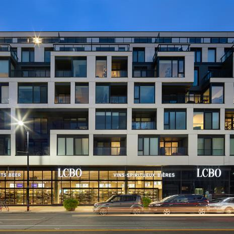 a white midrise condominium building with cube-like balconies and windows in a random pattern, with an LCBO on the ground floor