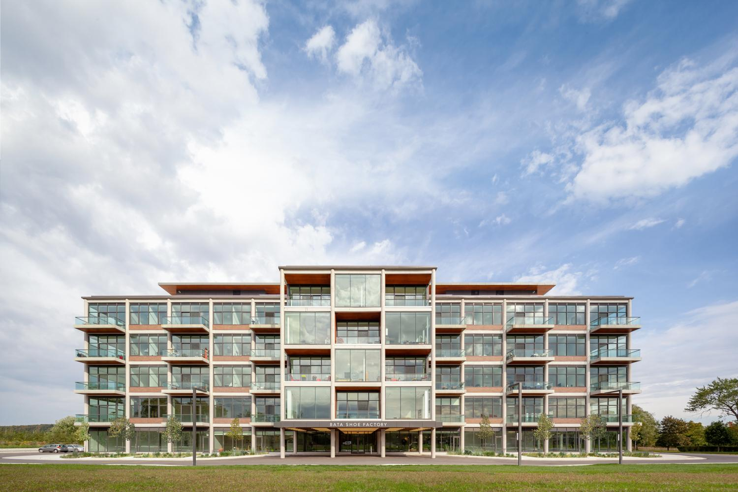 clouds and blue sky and green grass around the converted Bata Shoe Factory residential condominium building, which retains its post modern factory bones