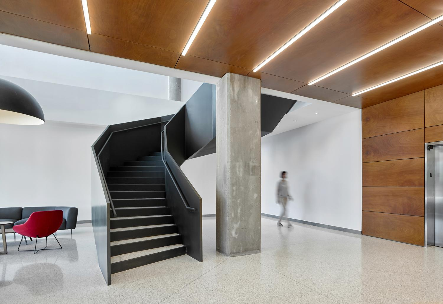 inside Bata Shoe Factory condo building showing black steel curving staircase, concrete pillar, and wood panel framed elevator bay and ceiling with inset LED strip lights