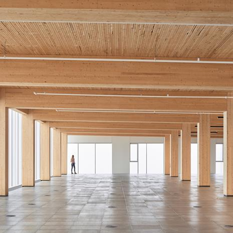 inside 80 Atlantic while the office floors are empty, showing long floorplate with exposed wood ceiling and columns and a woman looking out a window obscured by white fog