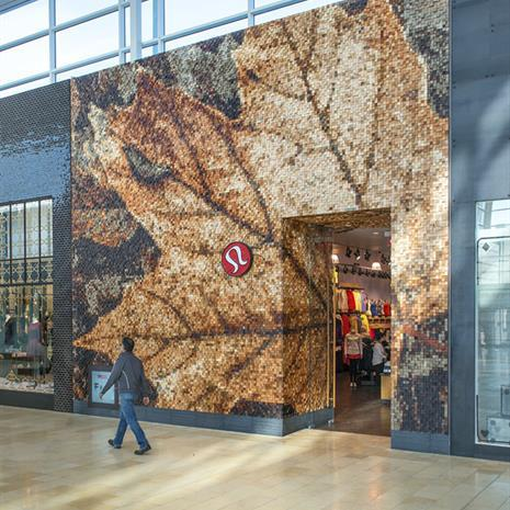 Lululemon storefront in a mall, made of wood in the shape of a maple leaf