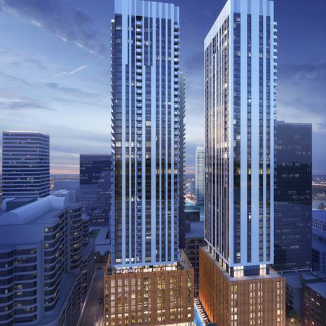 rendering of two high-rise towers atop brick podiums with a row of Victorian townhouses in front