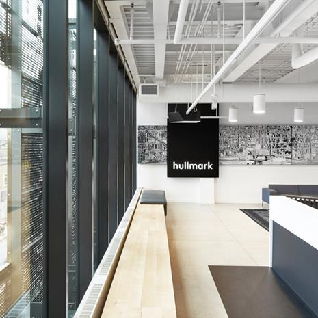"""the lobby of a minimalist black and white decorated office with a black wall hanging with the word """"hullmark"""""""