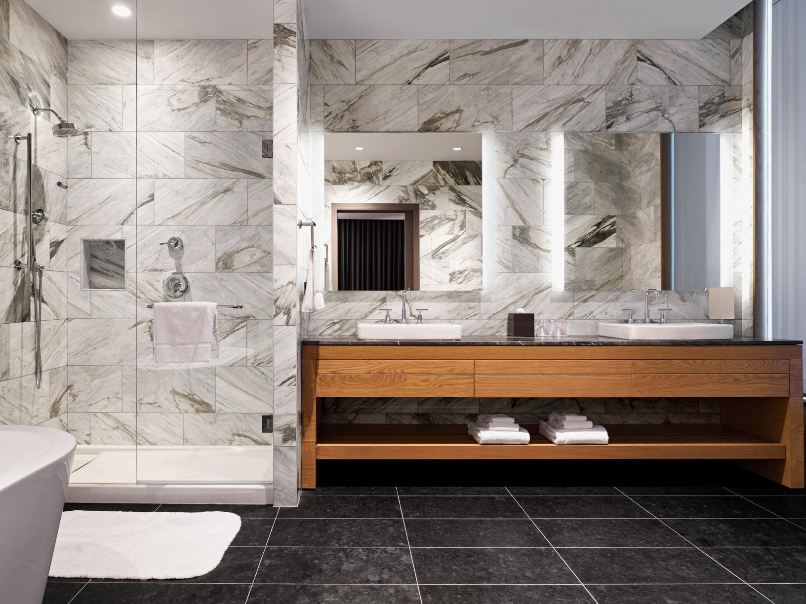 bathroom with his and hers vanity, white marble shower and black floor tiles