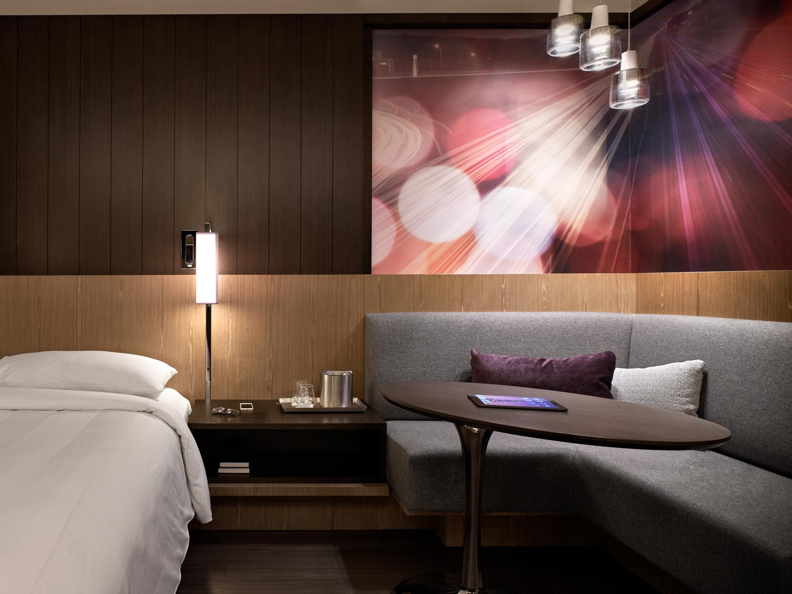 standard hotel suite showing partial bed, wooden nightstand, and adjacent grey corner seating with pink and purple artwork above