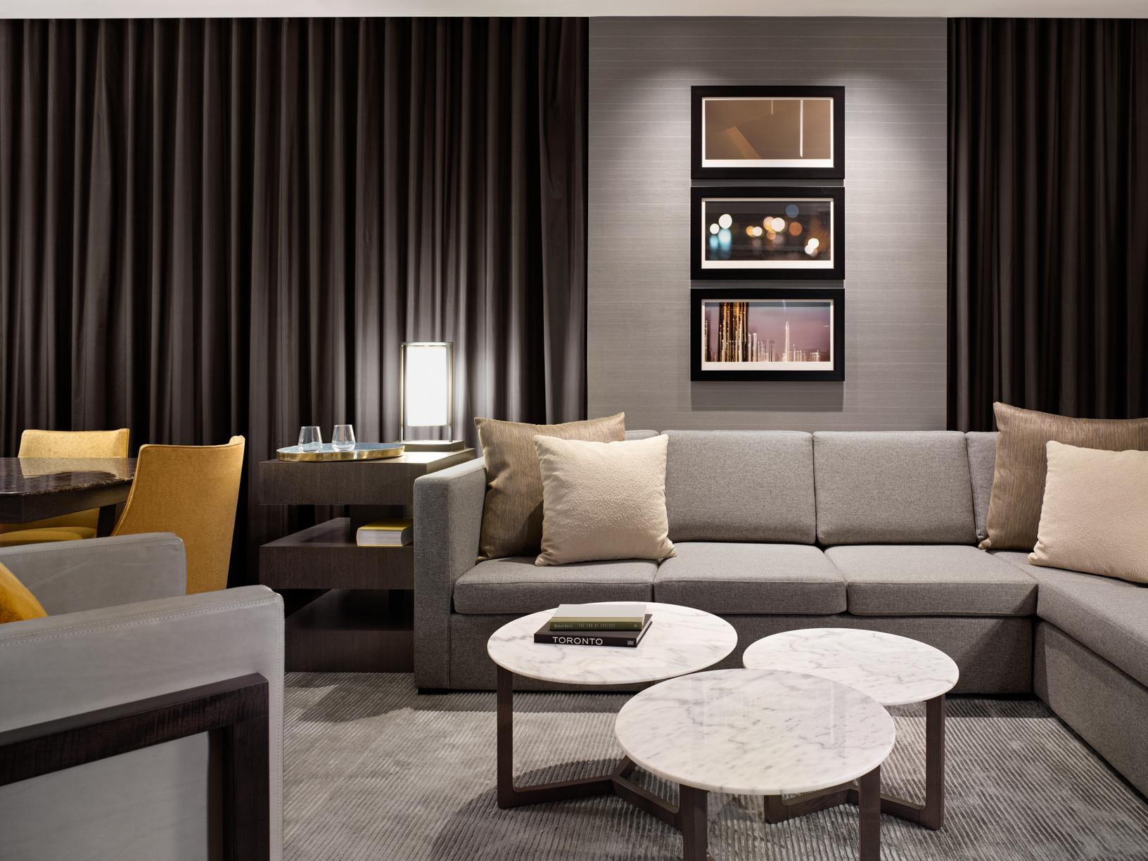 sitting area in a hotel suite with grey couch, white marble coffee table and yellow accent chairs and pillow