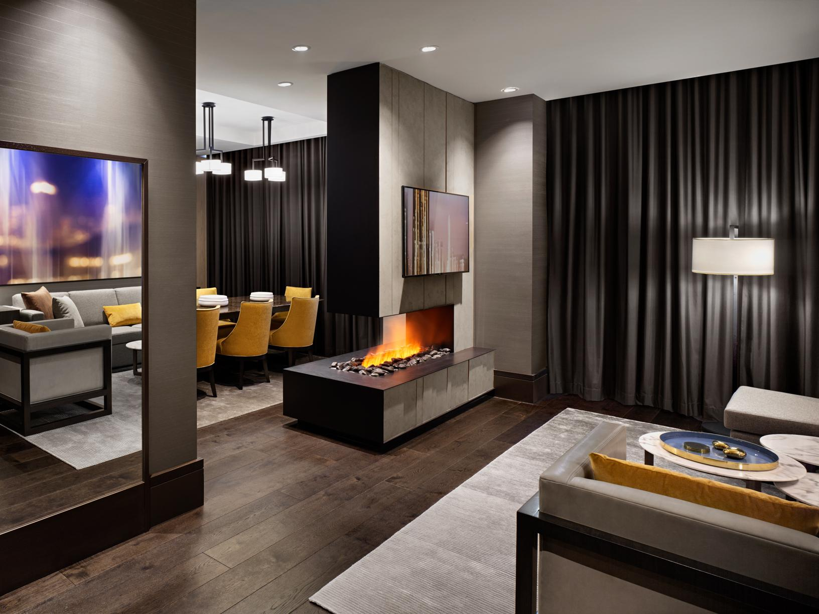 large hotel suite with dark hardwood floors showing a fireplace separating the living and dining areas with yellow accent furniture