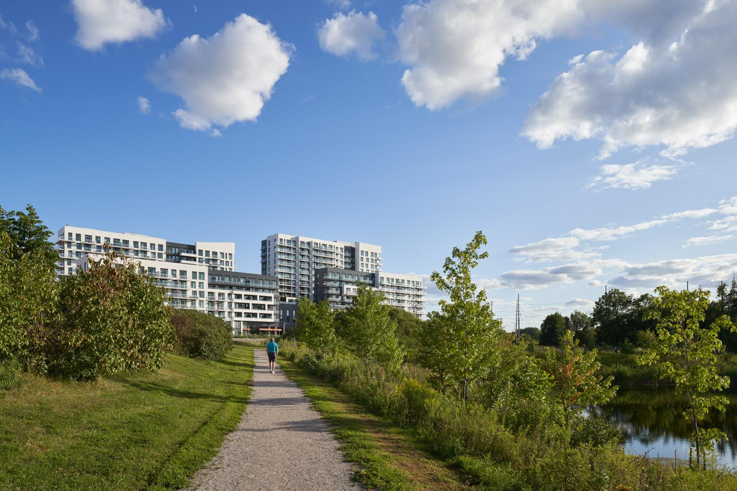 York Condos visible in the background as a man jogs along a path in a grassy nature-filled park