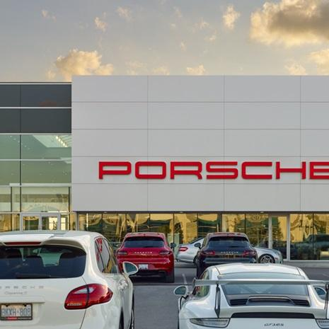 looking across a full parking lot to the side of a light grey clad Porsche dealership building