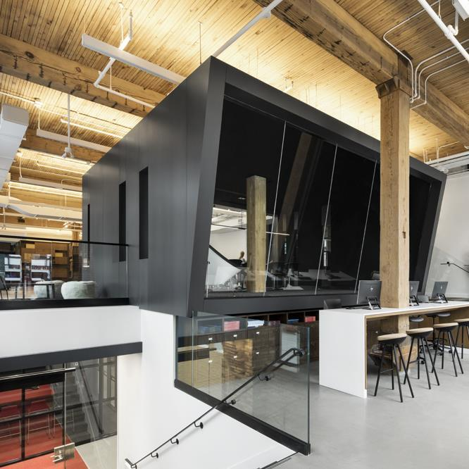 black framed boardroom cantilevered over a counter, in a three-leveled space with exposed brick and wooden beams