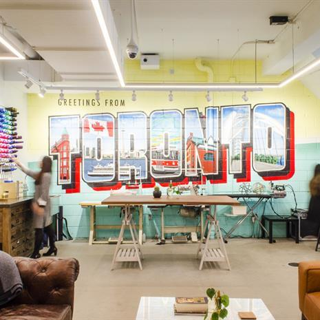 a room with leather couches, a workshop desk and a colourful wall mural of the word Toronto