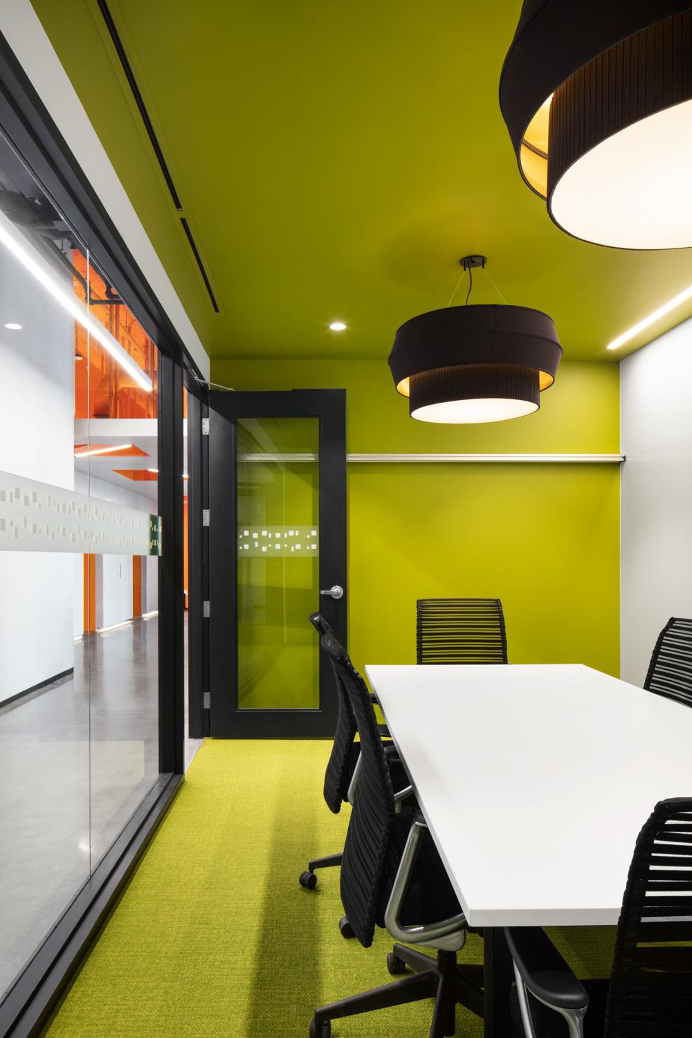a modern meeting room with lime green carpet, wallcovering, and ceiling