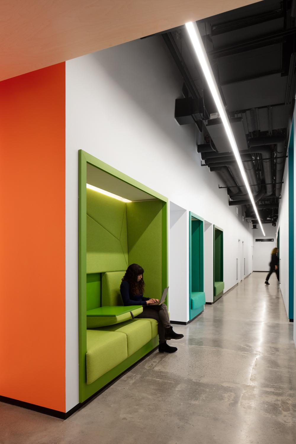 green and teal seating nooks recessed into the hallway wall in OCAD U CO