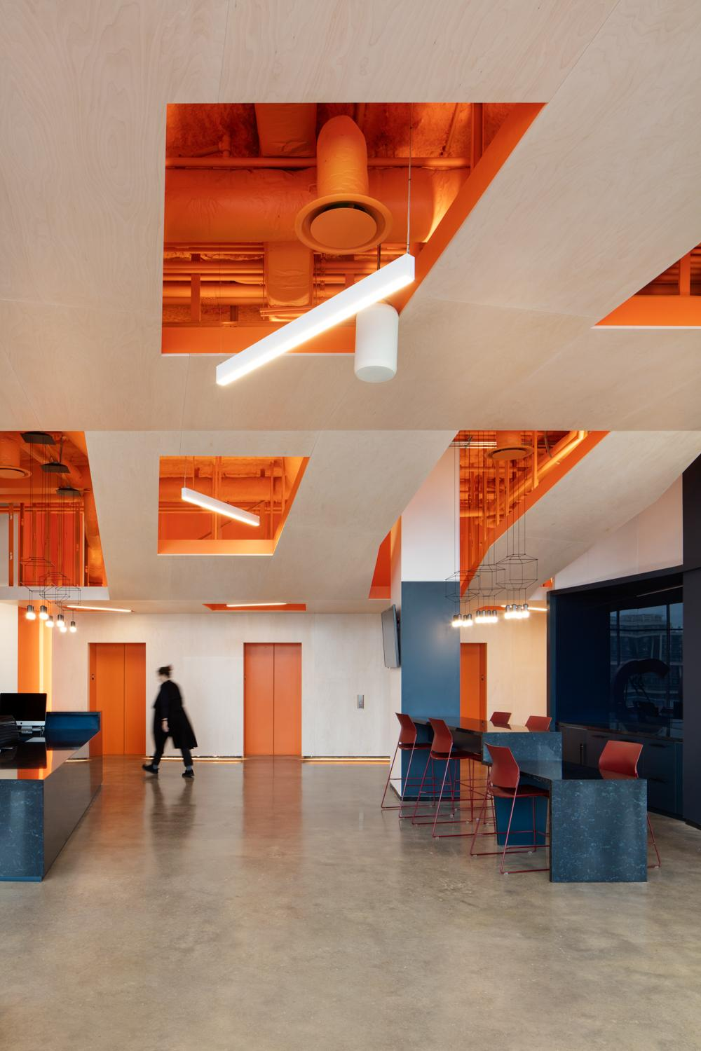 A woman walks by bright orange elevator doors in OCAD U CO under a dropped wood ceiling fixtures with cut outs revealing a matching bright orange ceiling