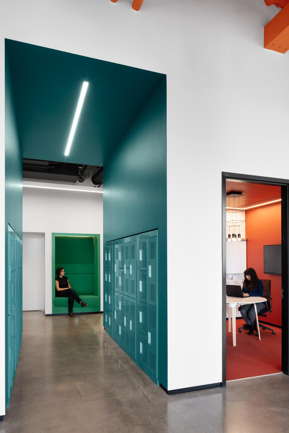 a woman sits in a recessed green seating nook in the wall, visible through a bright teal hallway with lockers, with another woman working on a laptop in a red meeting room visible to the right