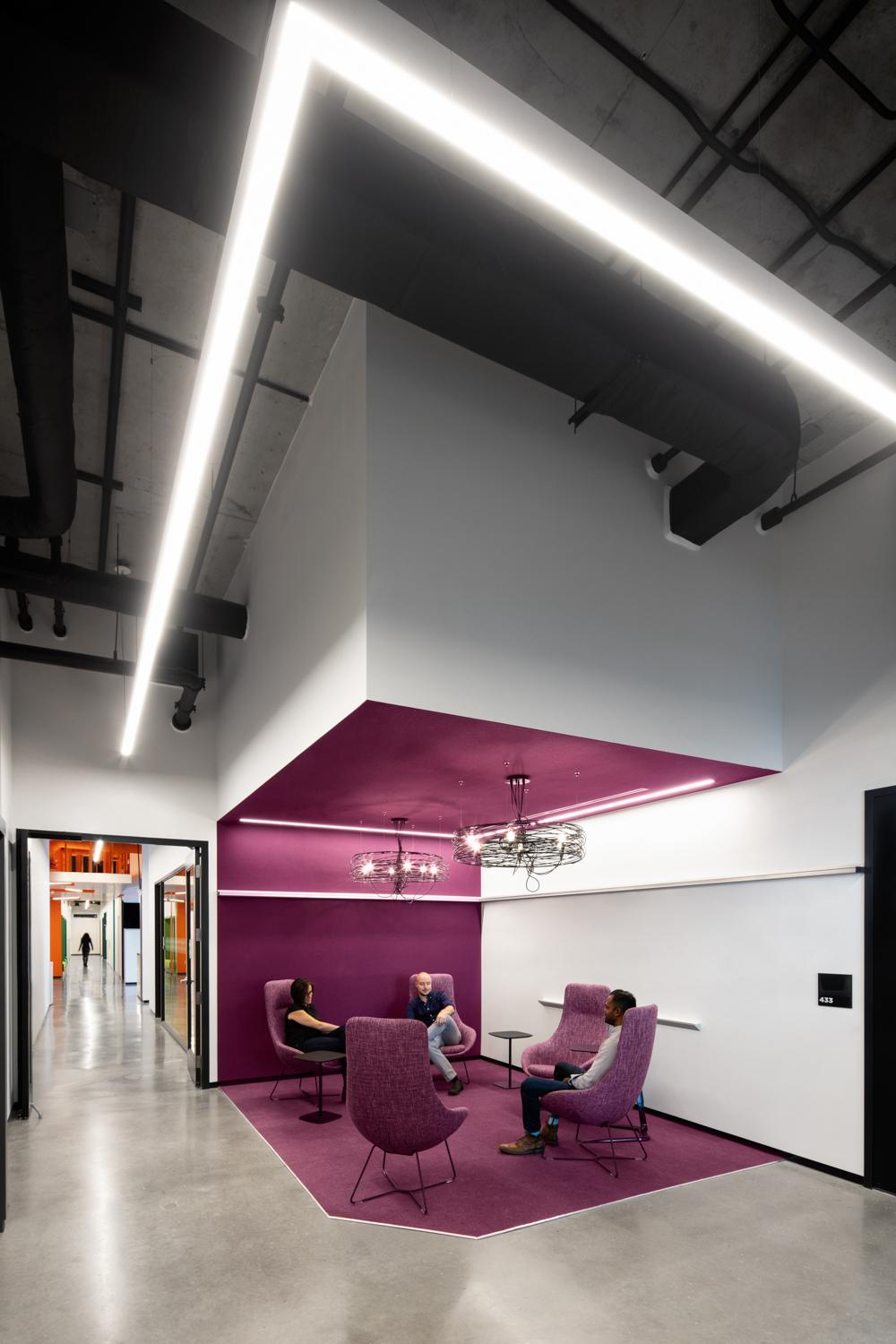 a plum coloured seating area in OCAD U CO with angular light fixture above