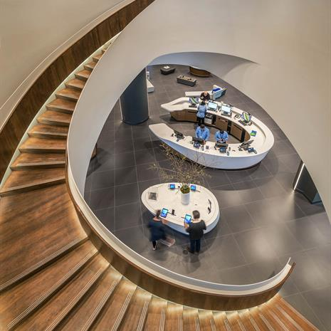 Looking down to the first floor from the second floor, through the opening of the curving wooden staircase which frames the white circular product tables and checkout point