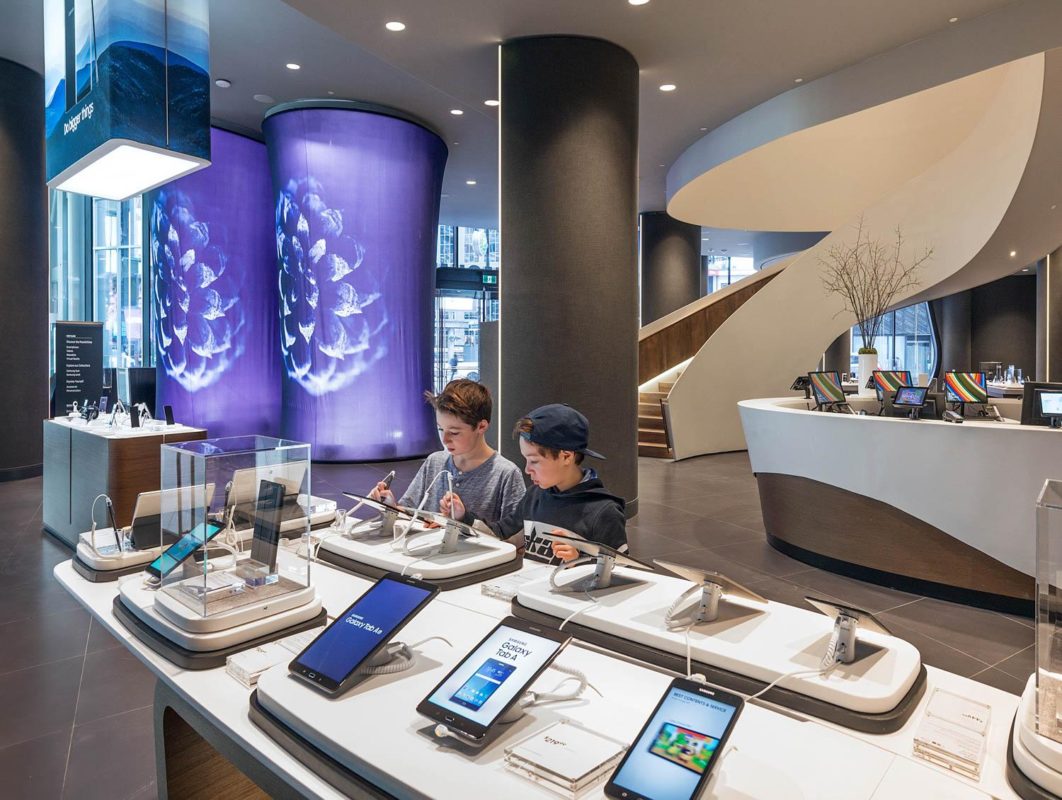 two boys play on the display smartphones in the Samsung Experience Store