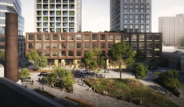 looking over an old factory building with smokestack, showing a landscaped parkette in front of a new condo building with two white clad residential towers atop a red brick podium with glazed retail at grade