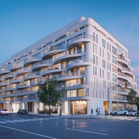 nine-storey midrise condo with light brick cladding and curved terraces
