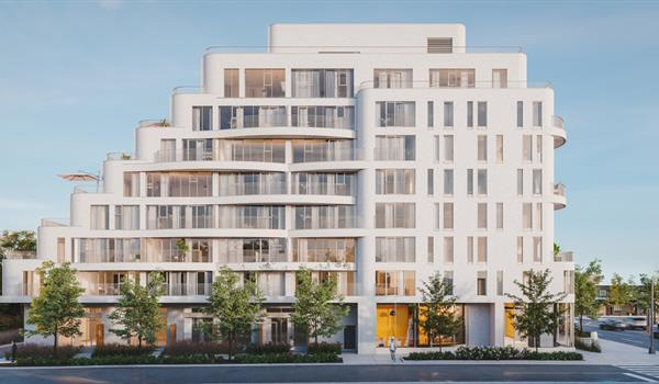 side view of a midrise condo with light coloured cladding and stepped terraces