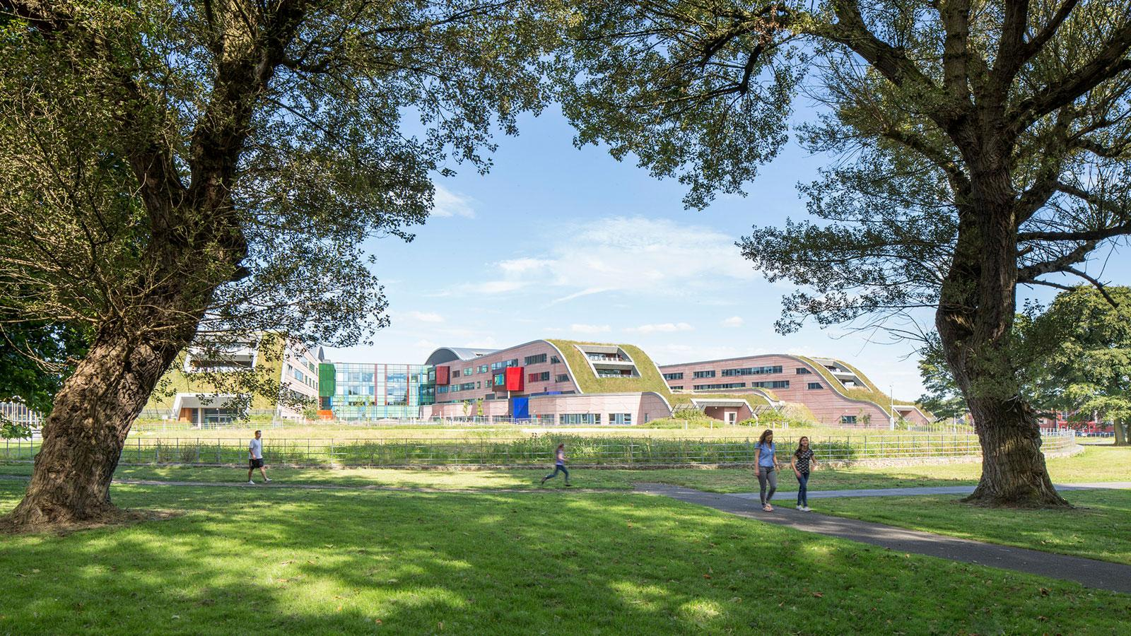 people enjoy a trail in the park on the ground of Alder Hey Children's Health Park hospital, with the building visible in the background