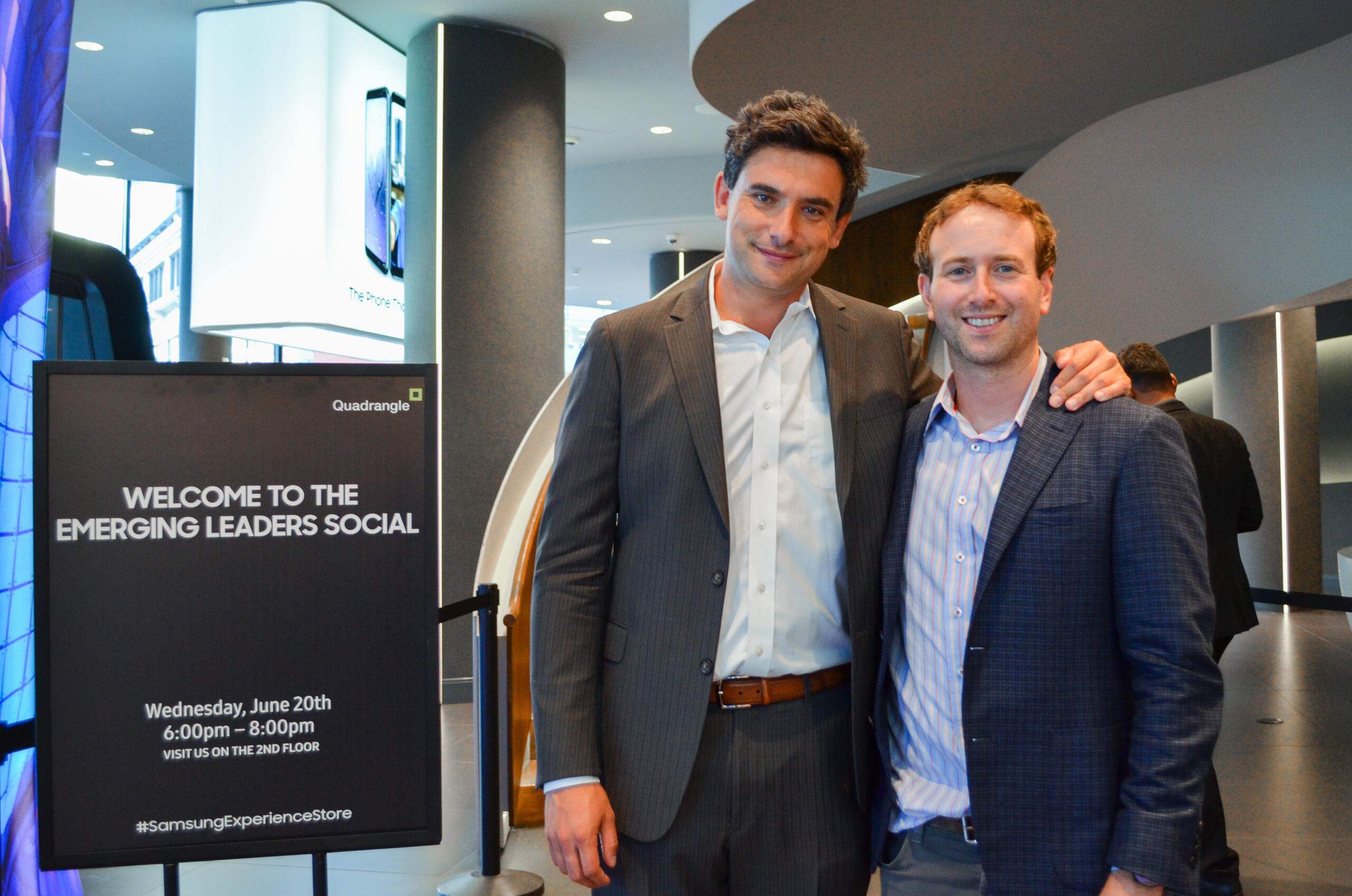 two men pose for a photo in front of a curving staircase and beside Emerging Leaders Social signage