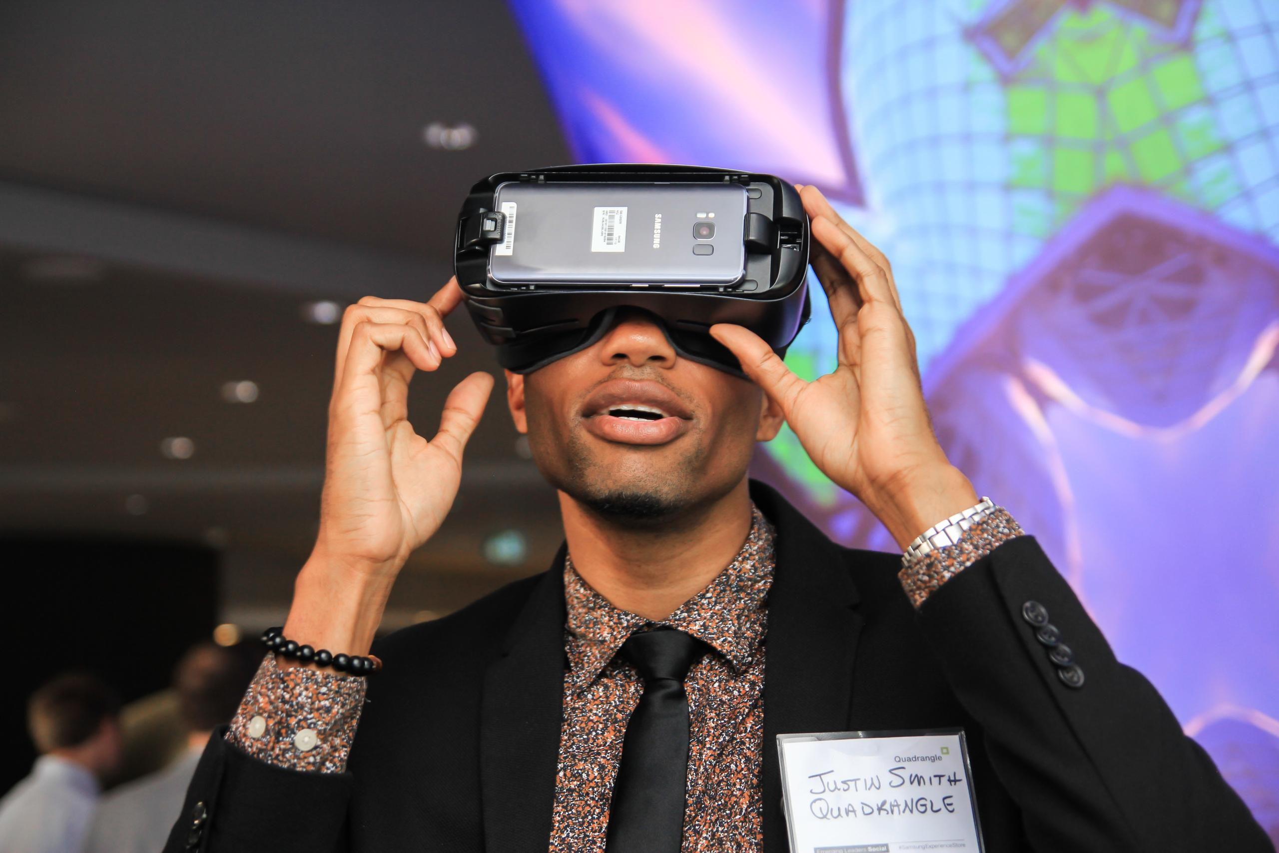 a well-dressed man wearing a Samsung VR headpiece