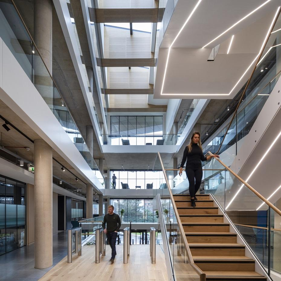 inside an office building with white, underlight feature staircase, and an atrium skylight