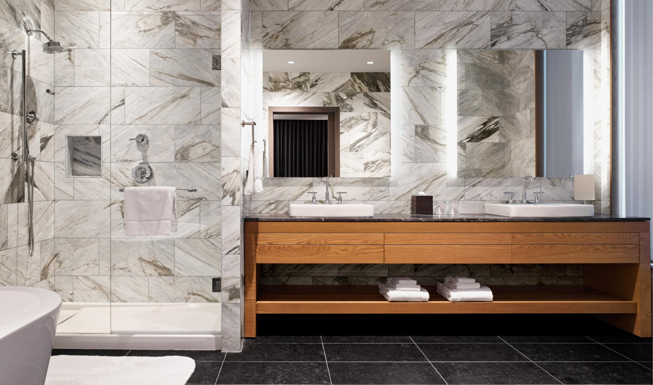 bathroom white white marble tile walls and inside the shower, black marble floors, and double vanity with wooden base