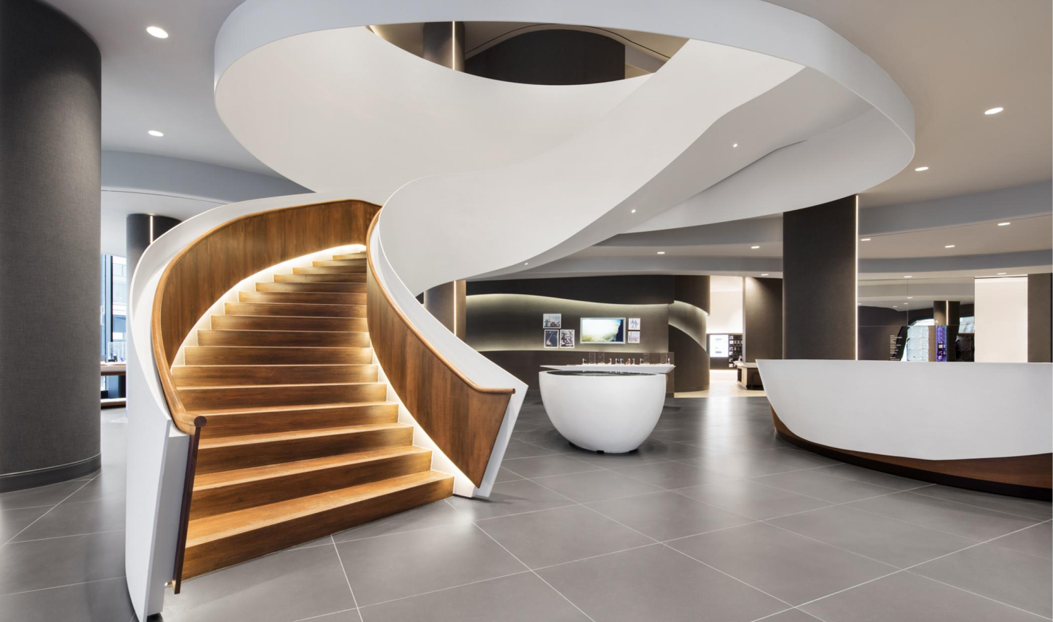 grand curving staircase framed in white steel with downlighting on the warm wooden steps