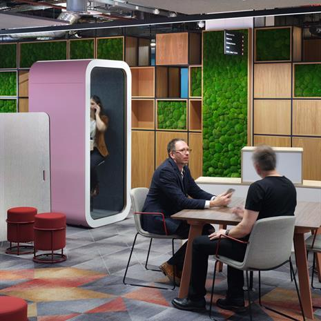 modern office with colourful geometric patterned carpet, millwork with built in green wall, men seated at a table, and woman in a modular phone booth