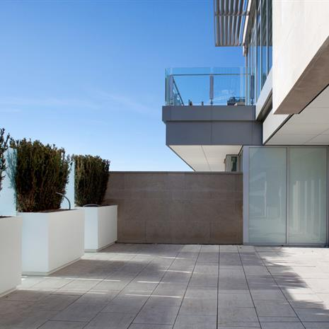 Balcony with planters integrated into glass railing.