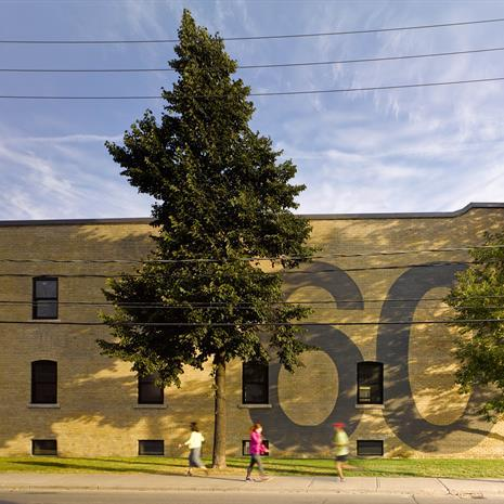 """The number """"60"""" painted on an exterior brick wall, spanning two storeys high"""