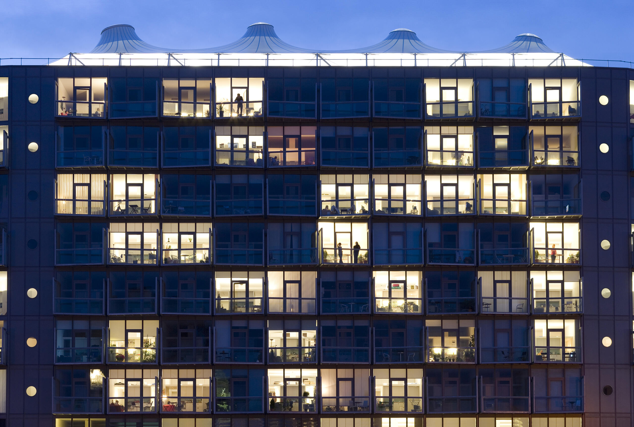 close up of the Abito Apartments facade at night showing a smattering of apartments with the lights on