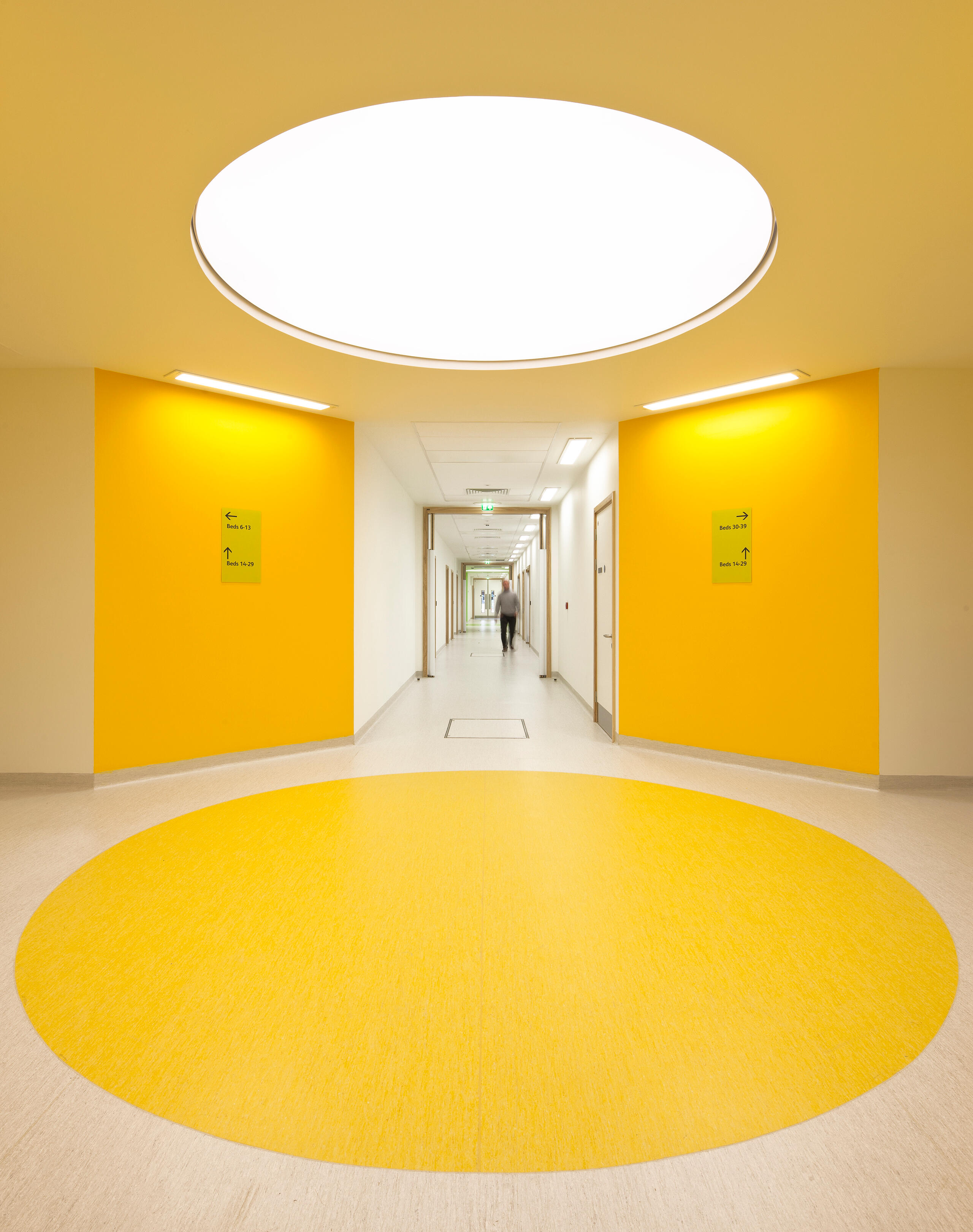 intersection of hallways inside Alder Hey Children's Health Park with yellow circle floor graphic, yellow walls and circular skylight above