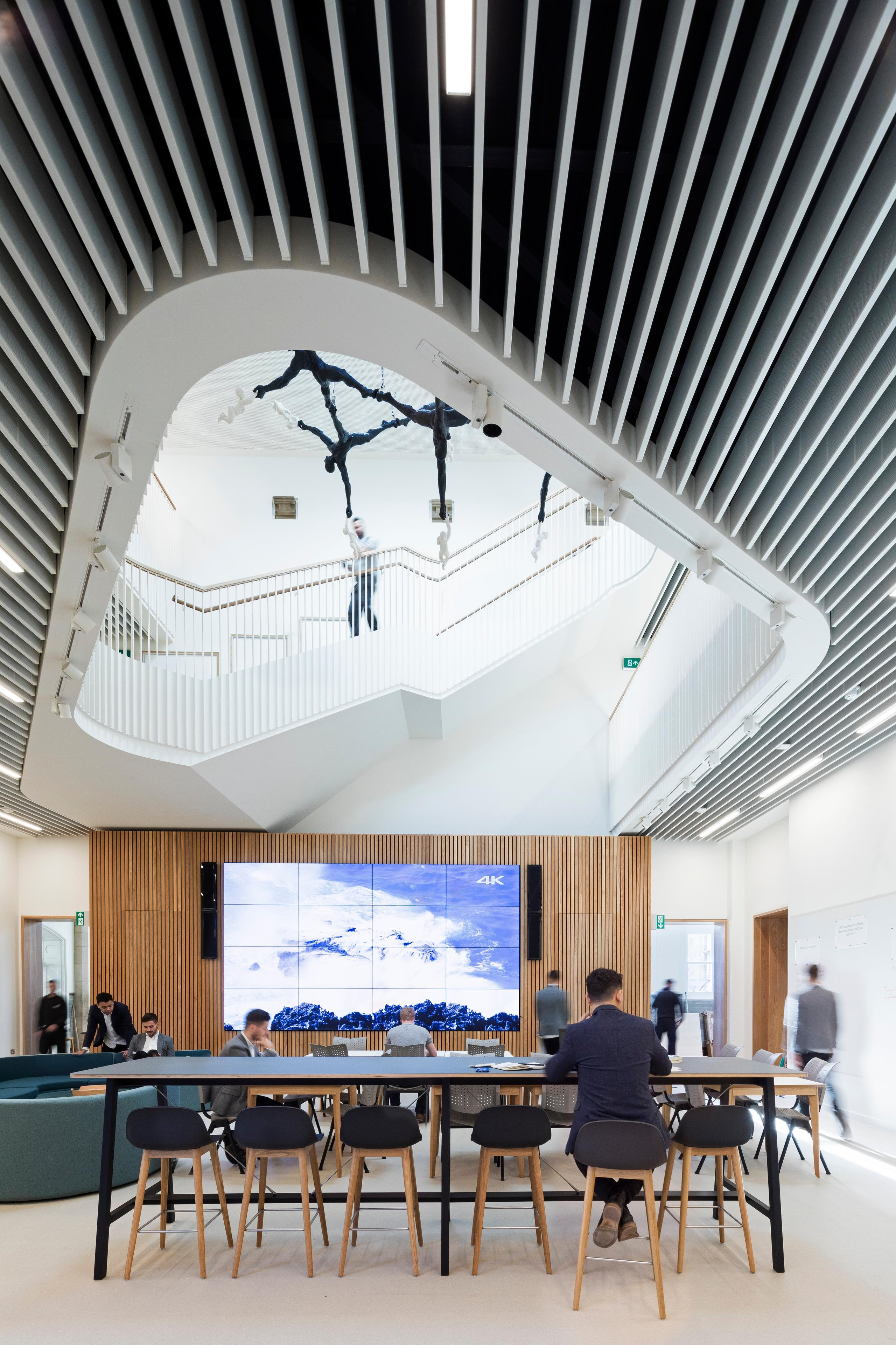 lobby of Barton Science Centre, with a mix of seating options, a flatscreen on a wood wall, and the upper storeys visible above in a round atrium cut out in the ceiling
