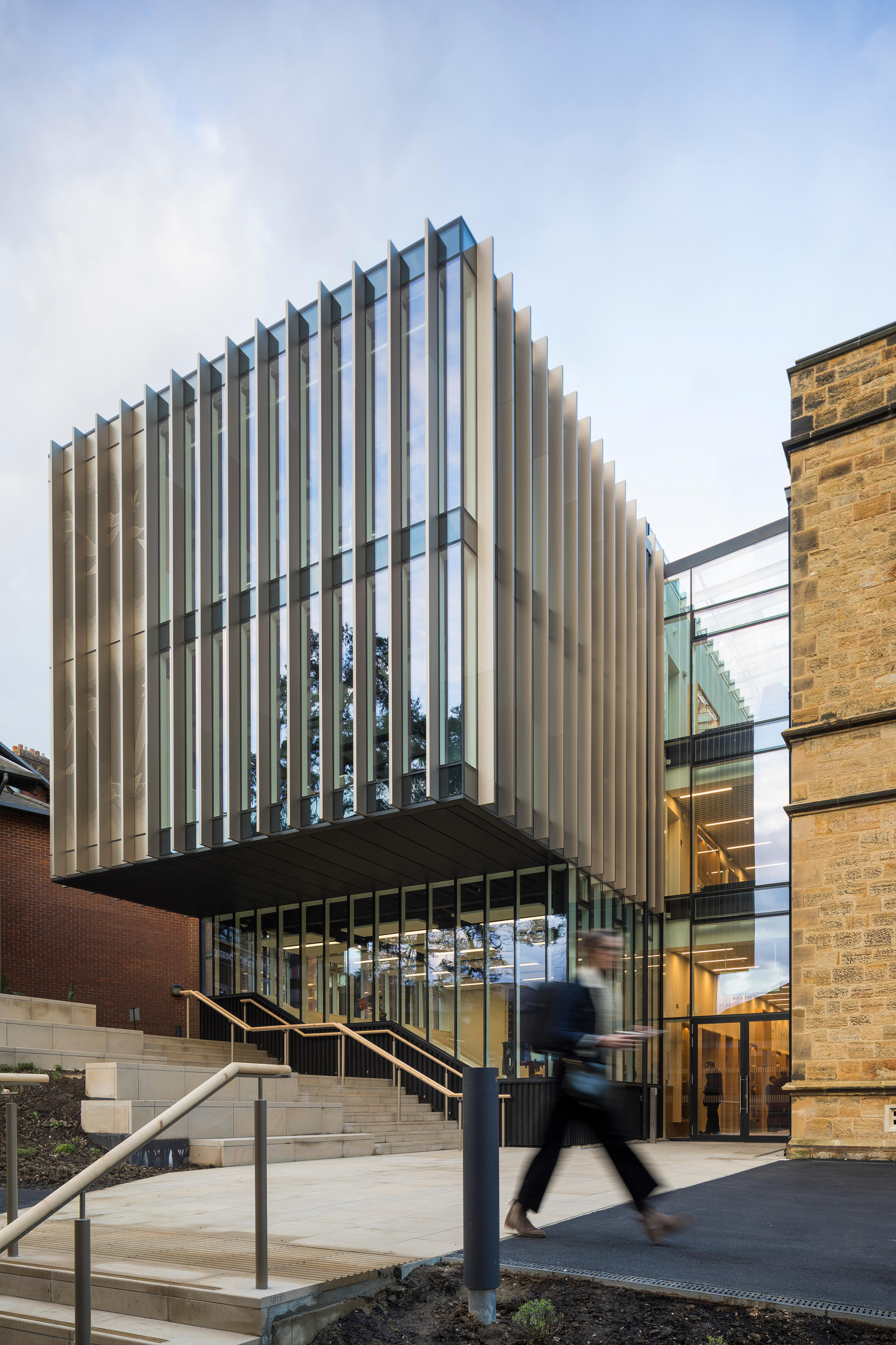 back of the new modern portion of Barton Science Centre, with a cantilevered section clad in vertical baguette fins, a glazed volume beside it and old lightly coloured heritage brick building portion connected to that