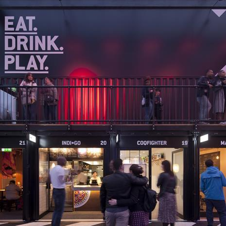 shipping container style outdoor retail market, with Eat Drink Play signage and people standing on a walkway above some retail outlets