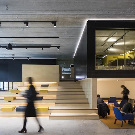 office interior with ampitheatre style seating and stairs, a raised black box studio space with glazing and further seating underneath
