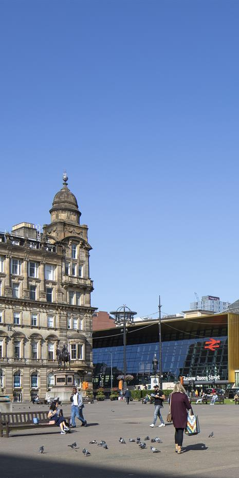 the modern glazed Glasgow Queen Street railway station seen from a distance with nineteenth century building and statue in the foreground