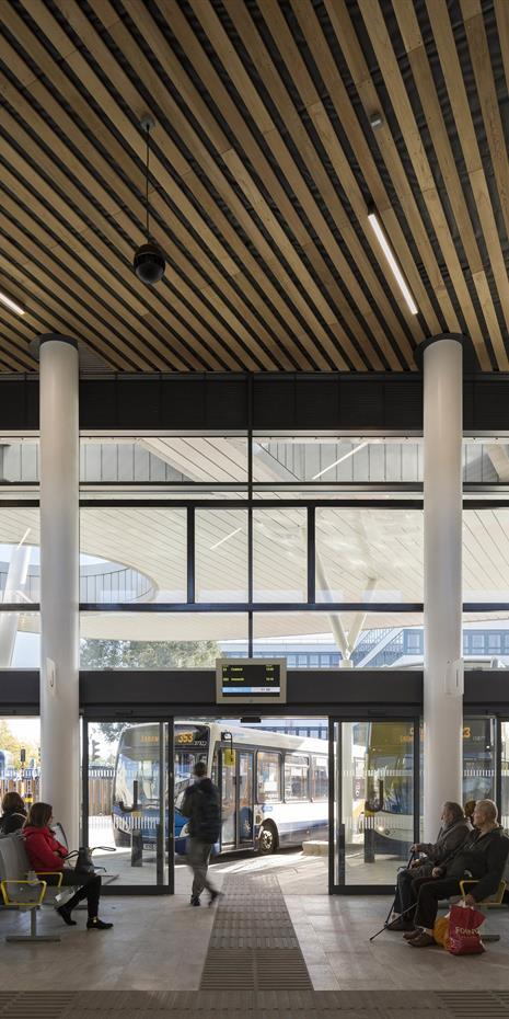 modern clean bus station with wooden slatted ceiling and generous windows