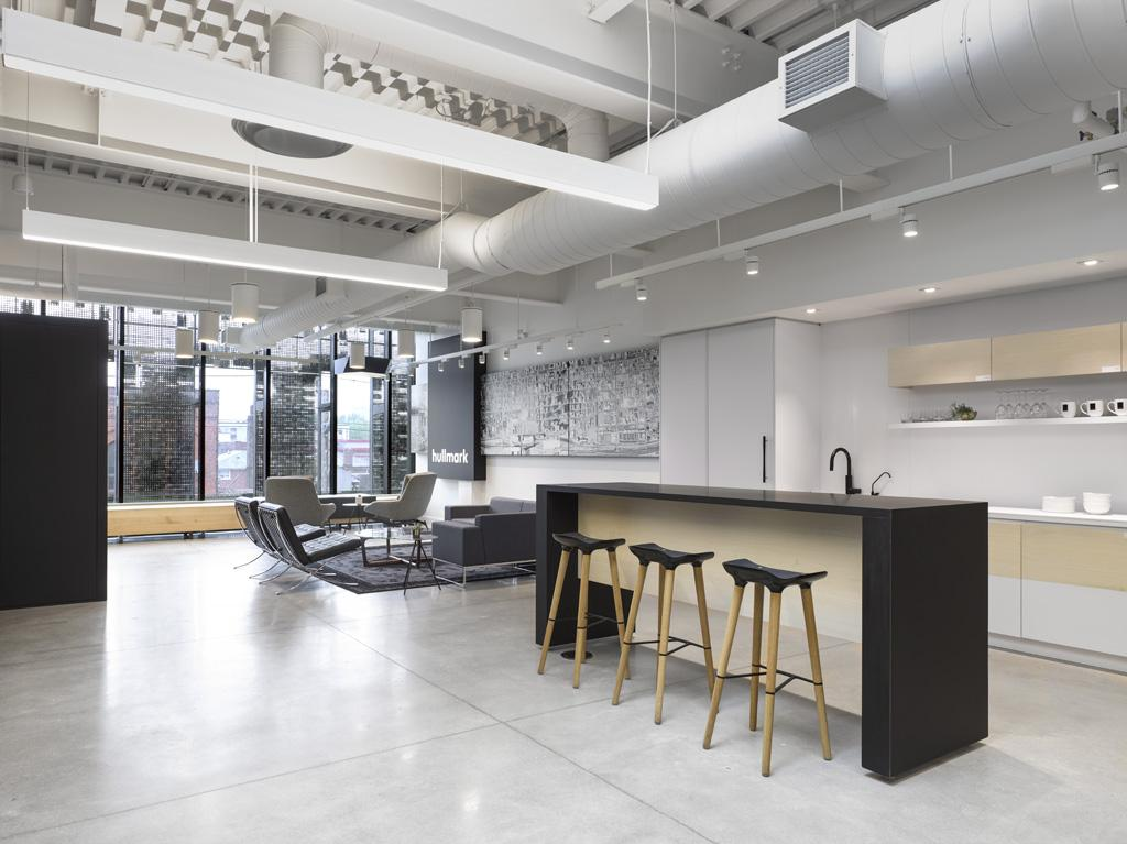 Black and white office interior showing kitchen with bar seating, reception seating area and windows