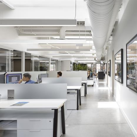 Office interior with a row of white work stations and skylights