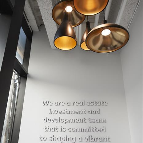 Ground floor entrance with mission statement on wall and five copper hanging lamps